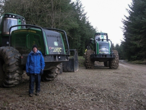 John is dwarfed by a huge logging machine