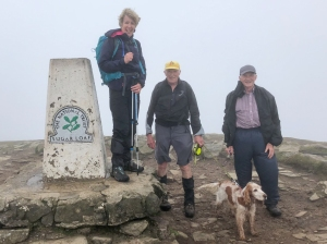 The trio and Pepper at a windy trig point